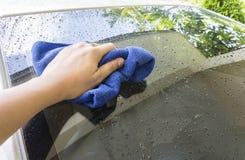 Hand mit blauem microfiber Stoff-Reinigungsauto Lizenzfreies Stockfoto