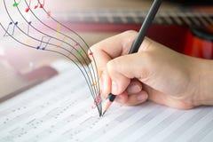 Hand mit Bleistift und Musikblatt Stockbild