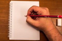 Hand mit Bleistift und Notizbuch Stockfotografie