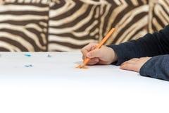 Hand mit Bleistift-Zeichnungs-Herzen Stockfotografie