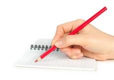 Hand mit Bleistiftschreiben auf Notizbuch Lizenzfreie Stockbilder