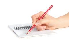 Hand mit Bleistiftschreiben auf Notizbuch Lizenzfreies Stockbild