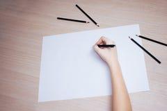 Hand mit Bleistiftschreiben auf Weißbuchblatt Lizenzfreie Stockbilder