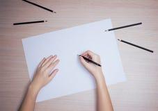 Hand mit Bleistiftschreiben auf Weißbuchblatt Lizenzfreie Stockfotografie