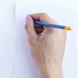 Hand mit Bleistiftschreiben in einem Notizbuch Lizenzfreies Stockfoto