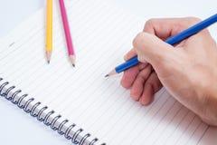 Hand mit Bleistiftschreiben etwas auf weißem Hintergrund Stockfotos