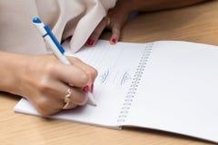 Hand mit Bleistiftschreiben im Notizbuch auf Holztisch Lizenzfreie Stockbilder