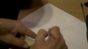 Hand mit Bleistiftschreiben im offenen Buch Nahaufnahmehände des Mannes Bleistift halten und auf Weißbuch in der Draufsicht zeich stock video