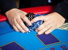 Hand mit Chips und $-Banknoten auf Tabelle Stockfotografie