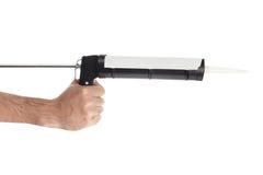 Hand mit dem Abdichtengewehrwerkzeug lokalisiert stockbilder