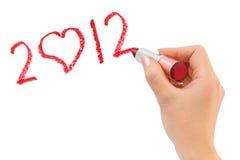 Hand mit dem Lippenstift, der 2012 zeichnet Stockfotos