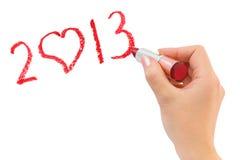 Hand mit dem Lippenstift, der 2013 zeichnet Stockbilder
