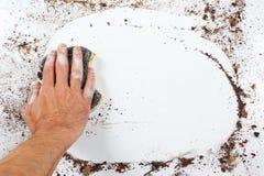 Hand mit dem nassen schwarzen Schwamm, der schwer schmutzige Oberfläche abwischt Lizenzfreie Stockfotografie
