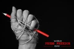 Hand mit dem roten Bleistift gebunden mit Seil stockbild