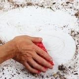 Hand mit dem roten Schwamm, der schwer schmutzige Oberfläche abwischt Lizenzfreies Stockfoto