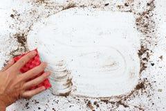 Hand mit dem roten Schwamm, der sehr schmutzige Oberfläche abwischt Lizenzfreies Stockbild