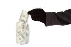 Hand mit dem schwarzen Handschuh, der Geld von einem Glas stiehlt Stockfotos