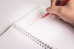 Hand mit dem Stift, der eine Liebe schreibt Stockfotos