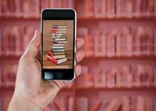 Hand mit dem Telefon, das Buchstapel gegen undeutliches Bücherregal mit roter Überlagerung zeigt Lizenzfreie Stockfotos