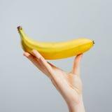 Hand mit den gemalten Nägeln, die eine Banane erfassen stockfotografie