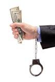 Hand mit den Handschellen, die US-Dollars anhalten Stockbilder
