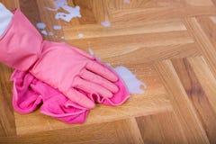 Hand mit den Handschuhen, die Boden abwischen Stockbilder