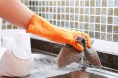 Hand mit den Handschuhen, die Edelstahlwanne mit Stoff abwischen Lizenzfreie Stockfotografie
