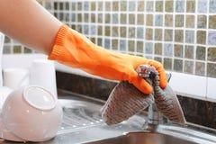 Hand mit den Handschuhen, die Edelstahlwanne mit Stoff abwischen Stockbild