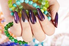 Hand mit den langen künstlichen manikürten Nägeln, die Armbänder halten stockfotos
