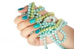 Hand mit den manikürten Nägeln, die farbige Halsketten halten Lizenzfreies Stockbild