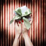 Hand mit den roten Nägeln, die eine Geschenkbox halten Stockbilder