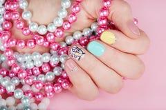 Hand mit den schönen manikürten Nägeln, die bunte Halsketten halten Lizenzfreie Stockbilder
