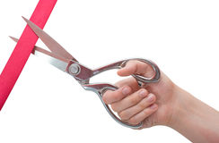 Hand mit den Scheren, die ein rotes Band schneiden stockfotos
