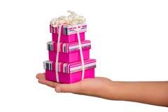 Hand mit den zusammengebundenen Geschenkkästen, getrennt auf Weiß Lizenzfreie Stockfotos