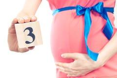Hand mit der Anzahl des dritten Monats der Schwangerschaft, erwartend für neugeborenes Konzept Stockbilder