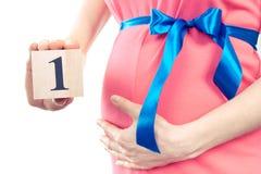 Hand mit der Anzahl des ersten Monats der Schwangerschaft, erwartend für neugeborenes Konzept Lizenzfreies Stockbild