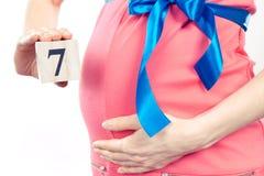 Hand mit der Anzahl des 7. Monats der Schwangerschaft, erwartend für neugeborenes Konzept Lizenzfreies Stockfoto