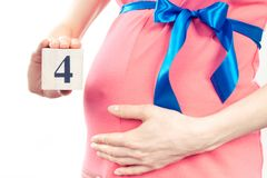 Hand mit der Anzahl des vierten Monats der Schwangerschaft, erwartend für neugeborenes Konzept Stockfotos