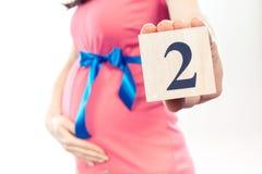 Hand mit der Anzahl des zweiten Monats der Schwangerschaft, erwartend für neugeborenes Konzept Stockbilder