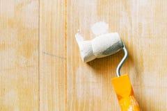 Hand mit der Farbenrolle, die Acryllack auf hölzernem Brett anwendet Stockbilder