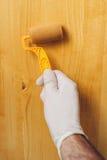 Hand mit der Farbenrolle, die Acryllack auf hölzernem Brett anwendet Stockfoto