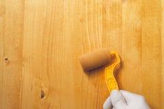 Hand mit der Farbenrolle, die Acryllack auf hölzernem Brett anwendet Stockbild