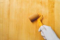 Hand mit der Farbenrolle, die Acryllack auf hölzernem Brett anwendet Stockfotografie