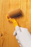 Hand mit der Farbenrolle, die Acryllack auf hölzernem Brett anwendet Lizenzfreie Stockfotografie