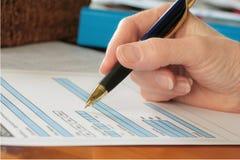 Hand mit der Feder, die blaues Formular ausfüllt Stockbilder