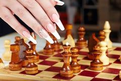 Hand mit der französischen Maniküre, die Schach spielt Lizenzfreie Stockfotos