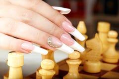 Hand mit der französischen Maniküre, die Schach spielt Lizenzfreie Stockbilder
