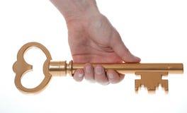 Hand mit der großen goldenen Taste getrennt auf Weiß Lizenzfreie Stockfotos
