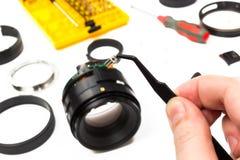Hand mit der Pinzette, die Teil des Kameraobjektivs hält Lizenzfreie Stockfotografie