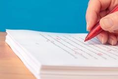 Hand mit der roten Feder, die eines Manuskriptes liest Stockfotos
